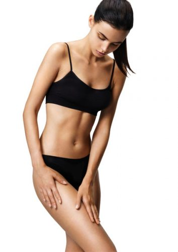 Beautiful girl in a black lingerie touches the delicate skin of her thighs. Young girl with perfect slim toned body. Health and beauty concept